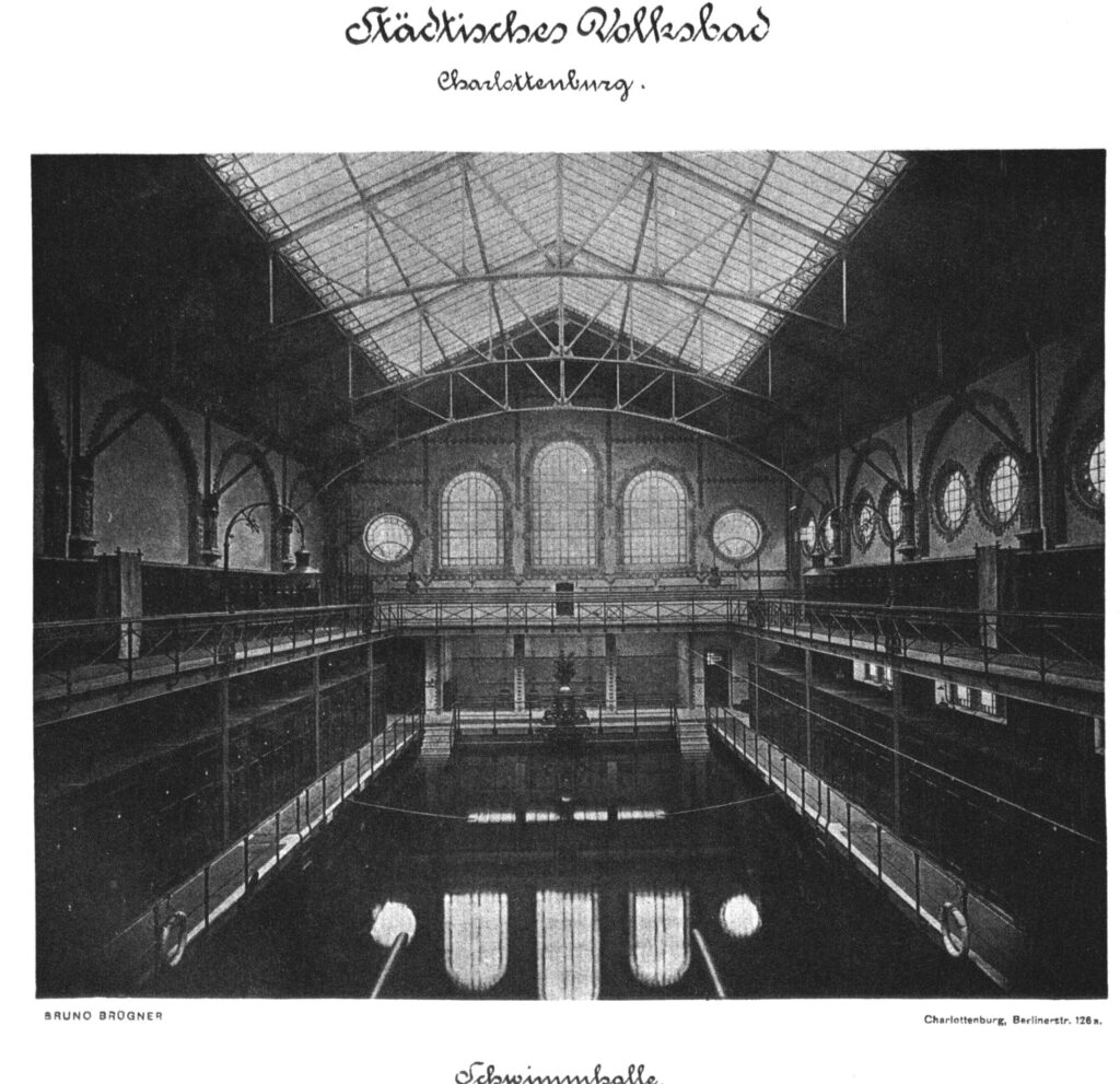 Foto der Schwimmhalle, Städtisches Volksbad Charlottenburg von der Galerie aus. Die Schwimmhalle ist leer, der Blick geht längs in Richtung Fenster.